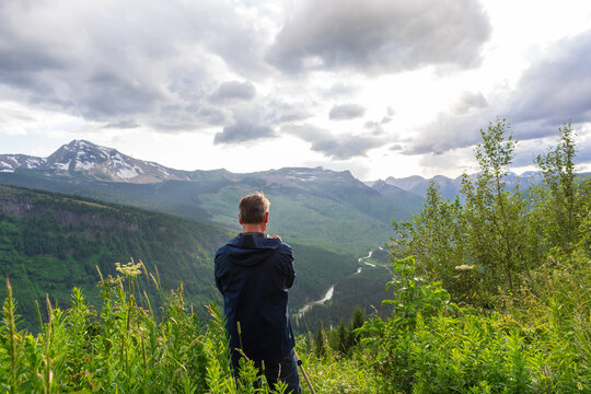 Backview of a man photographing a beautiful mountain landscape