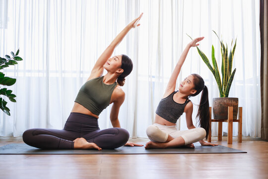 Asian young mother and her daughter setting prepare to yoga and meditation pose together on yoga mat in living room at home.