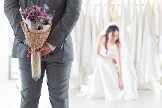 Asian woman in a bridal gown Smiling groom. The groom wearing gray suit  holds a purple bouquet of flowers to surprise the bride who sits in the fitting room. Concept wedding best day.