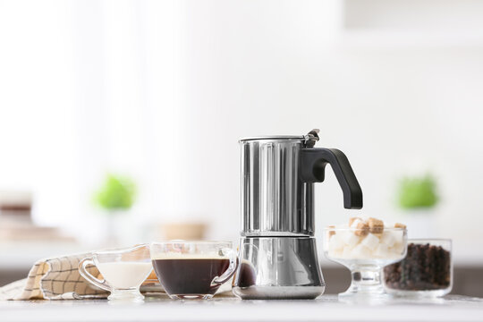 Coffee maker and cup of espresso on table in kitchen