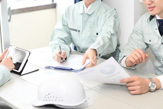 オフィスで会議をする作業服を着た男性と女性
