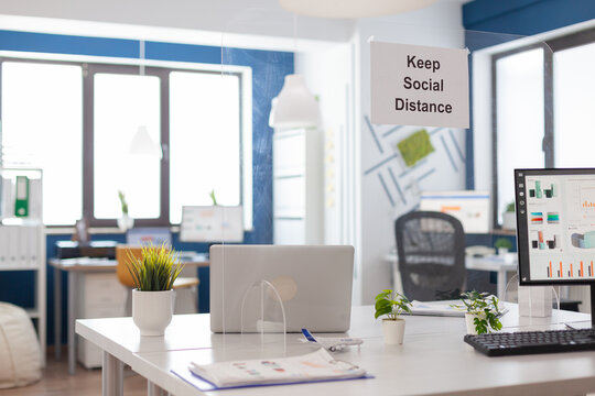 Modern empty office interior with plastic separators and keep social distance poster on the walls. Empty corporate space business interior with nobody in it.