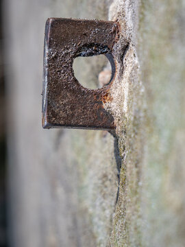 Detail of steel bolt anchor eye in sandstone rock. The end knot of steel rope