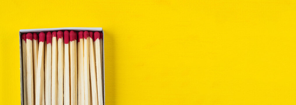 A box of matches on a yellow background close-up with a blank space for your text