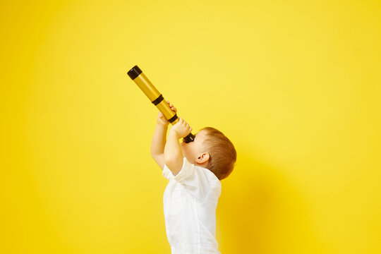 Side view of a child looking through a telescope on a yellow background. The concept of travel, pirates and adventures, active lifestyle, striving for the goal