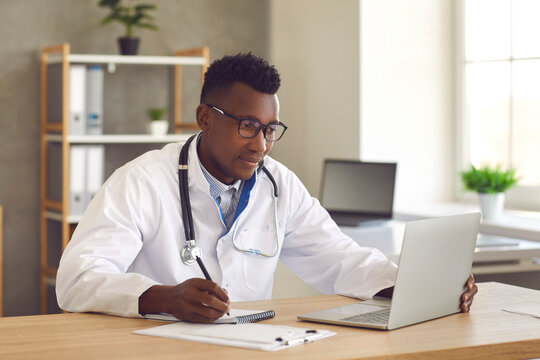 Remote medical help for distance patient, telemedicine, video call consultation. Young african american doctor medical professional working on laptop looking at screen and writing notes on paper