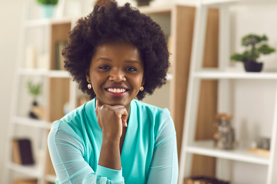 Providing online services. Close up portrait of a female company manager sitting in front of a webcam and holding an online meeting with her clients. Dark skinned woman communicates via video call.