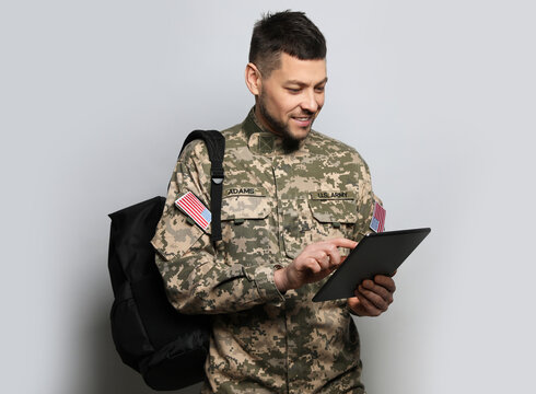 Cadet with backpack and tablet on light grey background. Military education