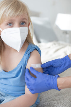 Close-up of a child, girl,boy, in hospital, doctor's office, where a plaster is put on her arm by a nurse. With mouth guard and FFP 2 mask.