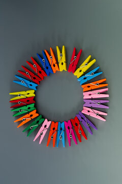 Conceptual composition, a group of multi-colored wooden clothespins arranged in a circle on a gray background.
