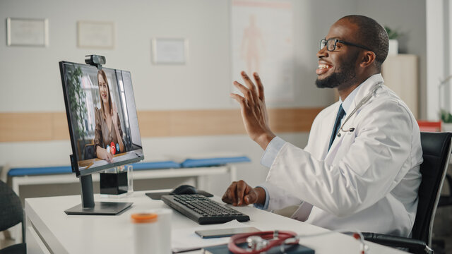 Doctor's Online Medical Consultation: Black Handsome Physician is Making a Video Call with a Female Patient on Desktop Computer. Health Care Professional Giving Advice, Explaining Test Results.