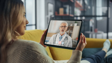 Close Up of a Female Chatting in a Video Call with Her Male Family Doctor on Digital Tablet from...