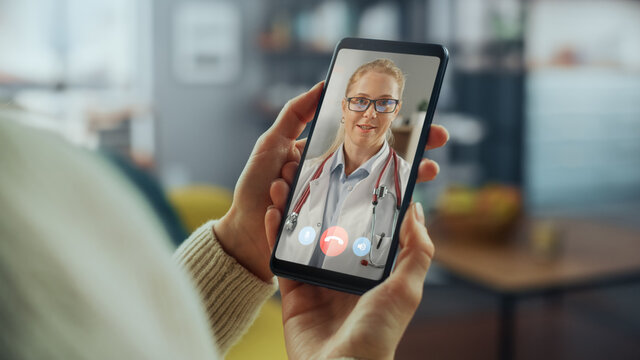 Close Up of a Female Chatting in a Video Call with Her Black Male Family Doctor on Smartphone from Living Room. Ill-Feeling Woman Making a Call from Home with Physician Over the Internet.