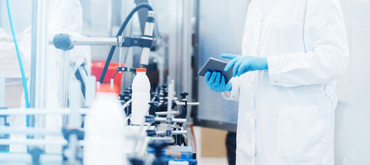 Fototapeta Worker inspecting production line bottle milk dairy factory with computer tablet. Concept food industry banner obraz