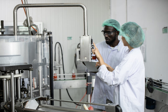 Woman staff worker working train African black man in food factory to operate the machine in clean production room.
