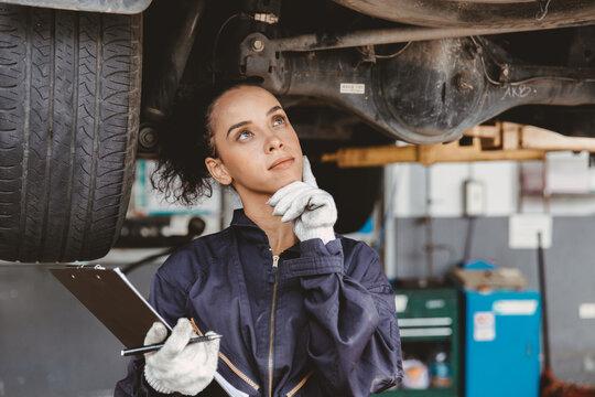 Women mechanic worker thinking. Garage staff female think day dream or forget check list auto service.