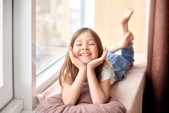Happy children day. Children Protection Day. smiling girl lies on windowsill on vacation