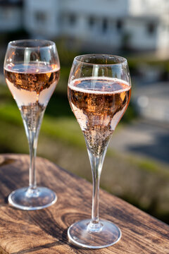 Drinking of rose champagne sparkling wine from flute glasses on outdoor terrace in France