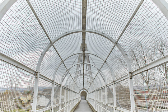 A long pedestrian tunnel with metal arches and mesh design. Aerial pedestrian crossing over the highway, perspective goes to the horizon, a empty tunnel no people