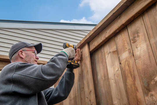 A middle-aged, white male constructs a tall wooden fence in his back yard.