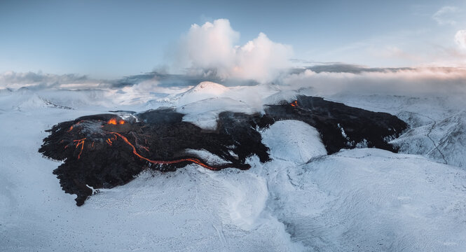 Aerial Panorama of active lava river flows from a volcanic eruption in mount Fagradalsfjall Geldingadalir valley, Southwest Iceland. Blue sky with snow mountains. The eruption is ongoing as of March