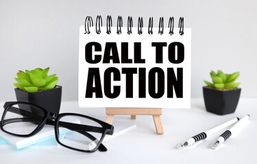 Call to Action. text on white paper, notebook on a stand on a light background near glasses and plants. business concept