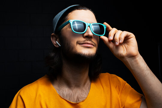 Studio portrait of smiling young man using wireless earphones wearing orange shirt, cyan sunglasses and grey hat on background of black brick wall.