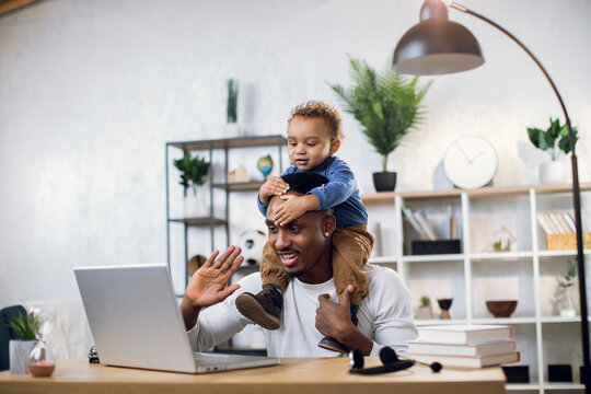 Handsome male freelancer smiling and waving during video chat on modern laptop. Young afro american father working from home and taking care of his little son.