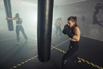 Boxer woman. Boxing fitness woman smiling happy wearing black boxing gloves. Portrait of sporty fit...