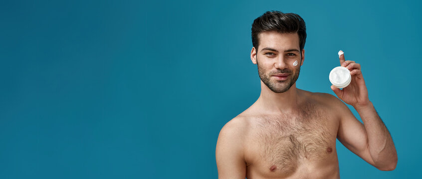 Attractive naked man with brown hair holding a white jar of beauty product, smiling at camera, posing with cream applied on his face isolated over blue background