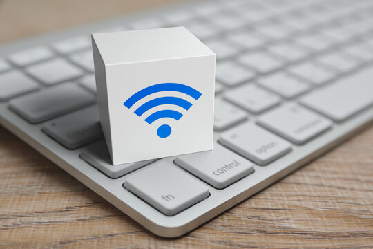 Wi-fi flat icon on white block cube with modern computer keyboard on wooden table, Technology internet communication concept
