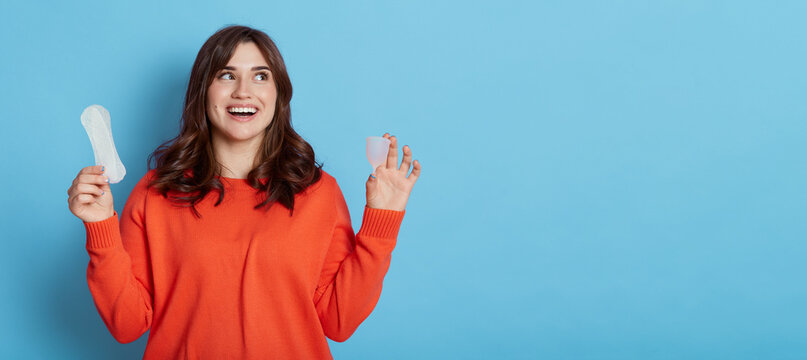 Happy excited dark haired female looking away with with toothy smile, comparing menstrual cap and cotton pad, copy space for promotion, isolated over blue background.