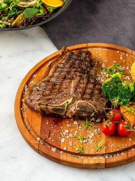 Medium rare Grilled T-Bone Steak with potato wedges, broccoli and wine on serving board block on dark background
