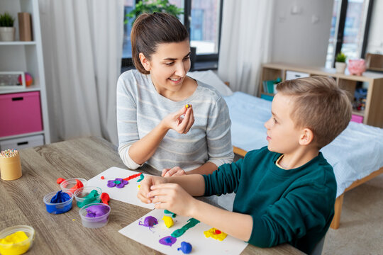 family, creativity and craft concept - mother and little son making picture of modeling clay at home