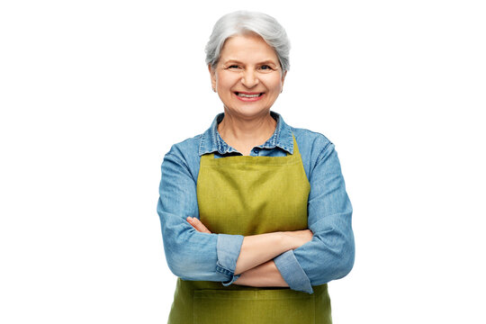 gardening, farming and old people concept - portrait of smiling senior woman in green garden with apron crossed arms over white background