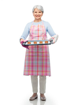 cooking, culinary and old people concept - smiling senior woman in kitchen apron with cookies on baking pan over white background