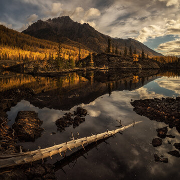 Sunrise at lake in mountain range. Beautiful reflection of clouds in water