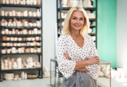 Successful lady. Confident mature business woman, entrepreneur smiling at camera, standing in her shop with arms crossed