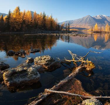 Sunrise at lake in mountain range. Beautiful reflection in water