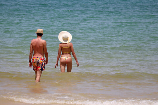 Couple in sunhats going to swim in the sea, rear view. Woman in bikini and man in shorts walking in waves, romantic holiday and beach vacation