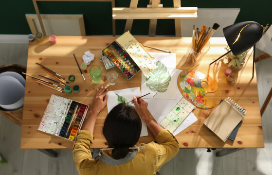 Young woman drawing leaf with watercolors at table indoors, top view