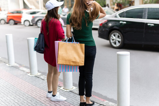 Two girlfriends in medical mask stand with shopping bags on the street.