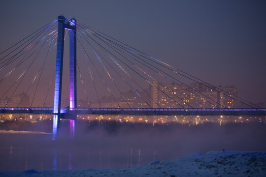 Bridge and fog across the river on the background of a beautiful sunset in winter