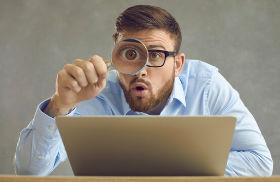 Portrait of funny handsome nerdy young business man in glasses sitting at office desk with laptop computer, holding magnifying glass and looking at something with big eye and surprised face expression