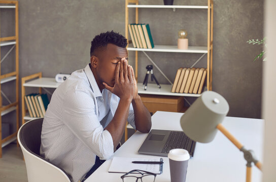Upset black man overwhelmed with problems, financial difficulties or stress and negativity at work. Tired and frustrated male student or office worker covers face sitting at desk with laptop computer