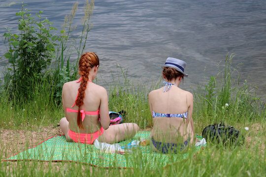 Two girls in bikini sitting on a green grass on a beach. Girlfriends at picnic on a river coast, spring or summer leisure on a nature, female friendship