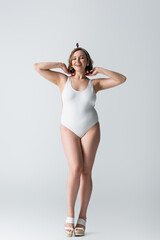 full length of cheerful overweight young woman in swimwear and earrings smiling while posing on...