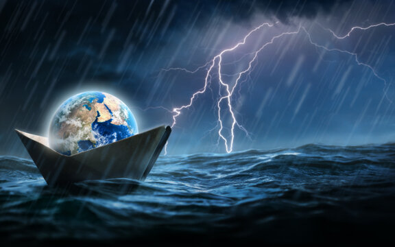 World in a paper boat floating in the ocean in a middle of a storm. Faith despite of world crisis and hardship conceptual theme.