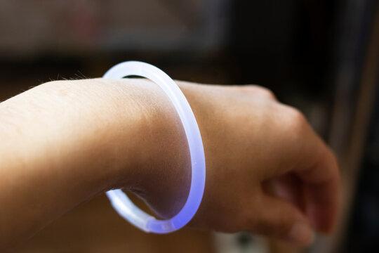 Purple neon bracelet on woman's hand closeup