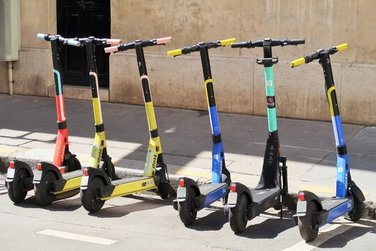 Plusieurs trottinettes électriques colorées en libre-service de la marque Dott stationnées sur un parking le long d'un trottoir à Paris – avril 2021 (France)